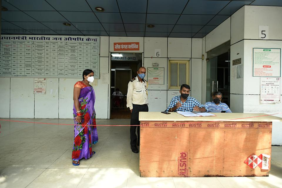 Four people in masks next to desk at black fungus clinic in Noida, India.