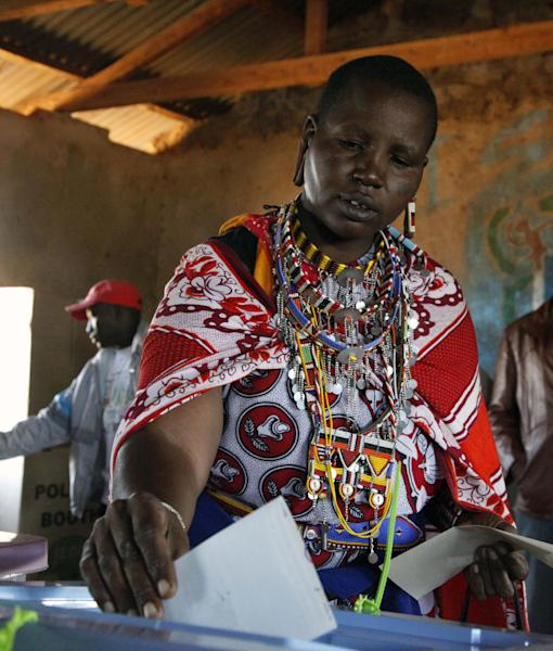 FILE--In this file photo of Monday March 4, 2013, A Masai woman casts her vote in a general election in Kajiado West, some 60 kilometers (37 miles) from Nairobi, Kenya. The chairman of Kenya's Independent Electoral and Boundaries Commission has refused to be sworn in before a parliament committee and stormed out of the hearing, breaking a pledge made this week that the commission would release all vote totals to the lawmakers Thursday, July 18, 2013. (AP Photo/Sayyid Azim, File)
