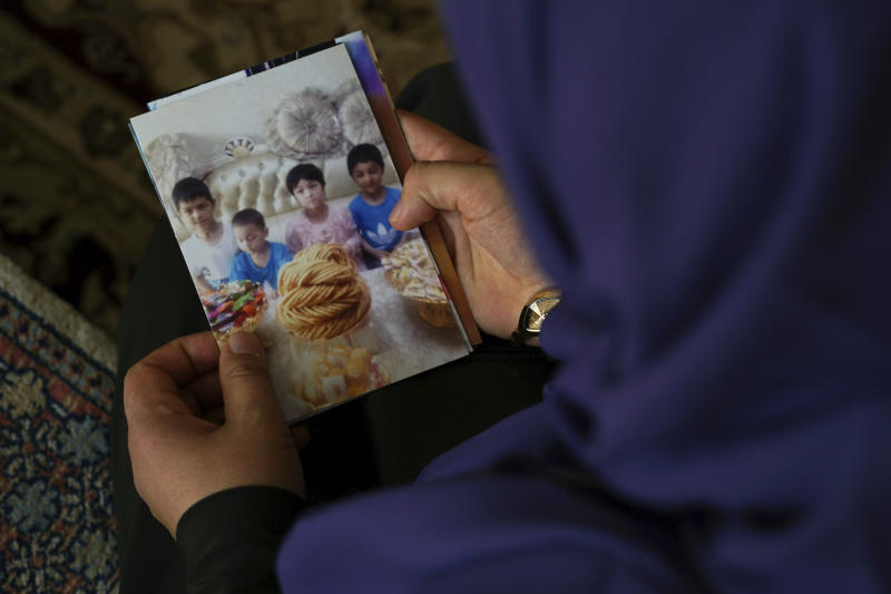 In this Aug. 20, 2018, photo, Meripet, 29, holds on to a photograph of her children in Istanbul, Turkey. Meripet came to Turkey in February 2017 to visit her sick father, leaving four children behind, her oldest son Abdurahman, 8, daughter Adile, 6, son Muhemmed, 4, and son Abdulla, 3. While in Turkey, she heard Uighur passports were being seized and that people who had gone abroad were being taken to reeducation – so she stayed in Turkey, giving birth to Abduweli. She hasn't seen her other four children since, and heard they were taken to a live-in kindergarten in Hotan, China. (AP Photo/Dake Kang)