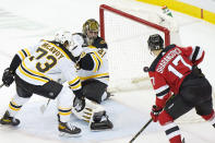 Boston Bruins goaltender Jaroslav Halak (41) looks over his shoulder as New Jersey Devils center Yegor Sharangovich (17) looks into the net at New Jersey Devils center Pavel Zacha's game-winning overtime goal in an NHL hockey game, Tuesday, May 4, 2021, in Newark, N.J.(AP Photo/Kathy Willens)