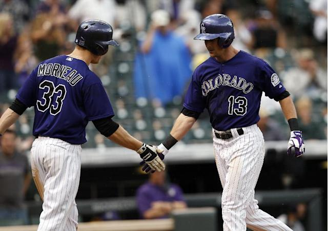 Colorado Rockies' Drew Stubbs (13) is congratulated by teammate Justin Morneau (33) after hitting a solo home run off San Diego Padres starting pitcher Ian Kennedy during the fourth inning of an MLB baseball game on Monday, July 7, 2014, in Denver (AP Photo/Jack Dempsey)