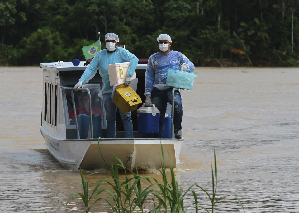 Healthcare workers Diego Feitosa Ferreira, 28, right, and Clemilton Lopes de Oliveira, 41, arrive on a boat to the Santa Rosa community, Amazonas state, Brazil, Friday, Feb. 12, 2021, to vaccinate residents with the Oxford-AstraZeneca COVID-19 vaccine. Navigating complex waterways to reach remote communities in Brazil's Amazon is only the first challenge for the healthcare workers vaccinating Indigenous and riverine people against the new coronavirus. (AP Photo/Edmar Barros)