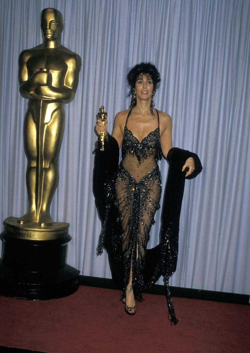 <p>Cher holds her Oscar for Best Actress in the film Moonstruck.</p>