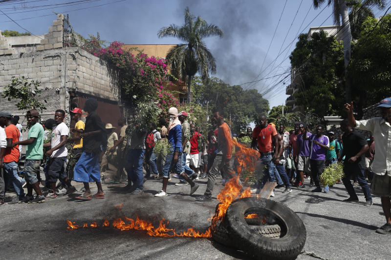 Demonstrators walk past a burning barricade during anti-government protests in Port-au-Prince, Haiti, Friday, Oct. 11, 2019. Protesters burned tires and spilled oil on streets in parts of Haiti's capital as they renewed their call for the resignation of President Jovenel Moïse just hours after a journalist was shot to death. (AP Photo/Rebecca Blackwell)