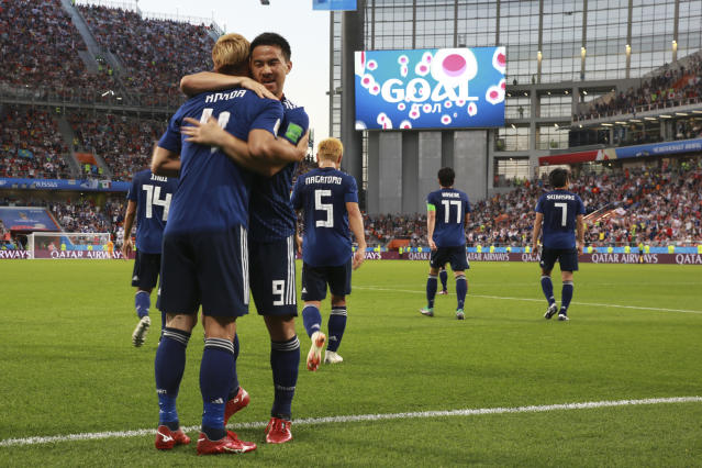Japan's Keisuke Honda, left, celebrates with teammate Shinji Okazaki after scoring his side's second goal during the group H match between Japan and Senegal at the 2018 soccer World Cup at the Yekaterinburg Arena in Yekaterinburg , Russia, Sunday, June 24, 2018. (AP Photo/Eugene Hoshiko)