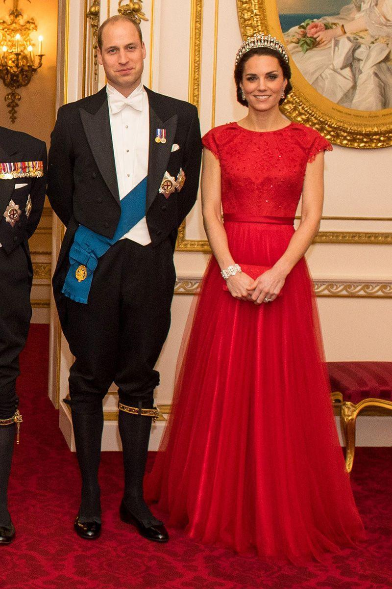 """<p>The Duchess wears a bright red cap-sleeved Jenny Packham dress with a red clutch, jeweled bracelet, pearl earrings and Princess Diana's famed <a href=""""https://www.harpersbazaar.com/celebrity/red-carpet-dresses/news/a19306/kate-middleton-wears-princess-diana-tiara/"""" rel=""""nofollow noopener"""" target=""""_blank"""" data-ylk=""""slk:Cambridge Lover's Knot tiara"""" class=""""link rapid-noclick-resp"""">Cambridge Lover's Knot tiara</a> at the Annual Diplomatic Corps Reception at Buckingham Palace.</p>"""