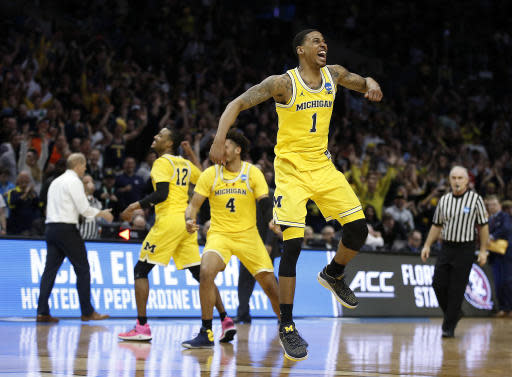 Michigan guard Charles Matthews (1), guard Muhammad-Ali Abdur-Rahkman (12) and forward Isaiah Livers (4) celebrate after Michigan defeated Florida State 58-54 in an NCAA men's college basketball tournament regional final Saturday, March 24, 2018, in Los Angeles. (AP Photo/Alex Gallardo)