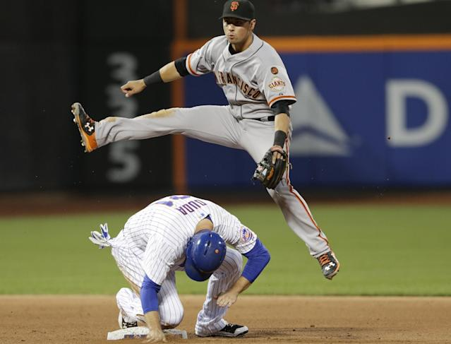 San Francisco Giants second baseman Joe Panik leaps over New York Mets' Lucas Duda after throwing out Michael Cuddyer at first base for a double play during the fourth inning of a baseball game Tuesday, June 9, 2015, in New York. (AP Photo/Frank Franklin II)