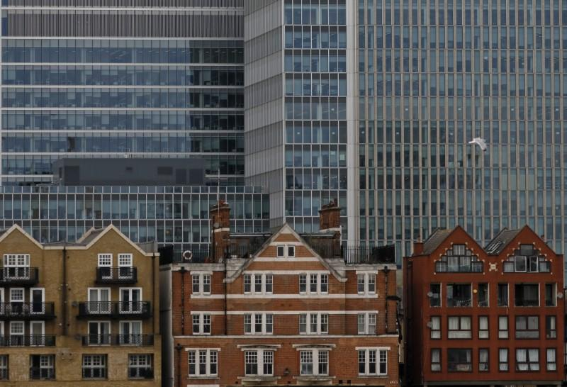 FILE PHOTO: Apartment buildings are backdropped by skyscrapers of banks at Canary Wharf in London