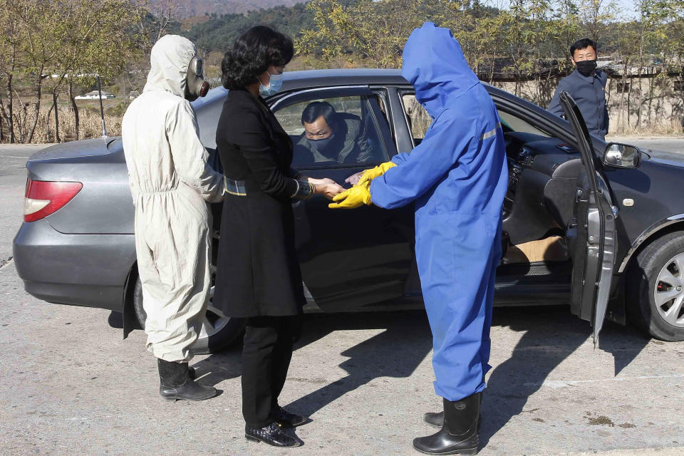Hygienic and anti-epidemic officials disinfect and check the temperature of people coming into the city of Wonsan, Kangwon Province, North Korea DPRK, on Wednesday, Oct., 28, 2020. (AP Photo/Jon Chol Jin)