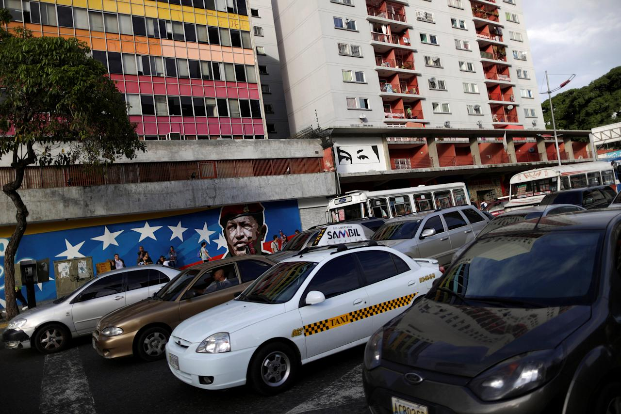 Venezuelan citizens walks past a mural depicting former Venezuela's late President Hugo Chavez in Caracas, Venezuela, December 1, 2016. REUTERS/Ueslei Marcelino