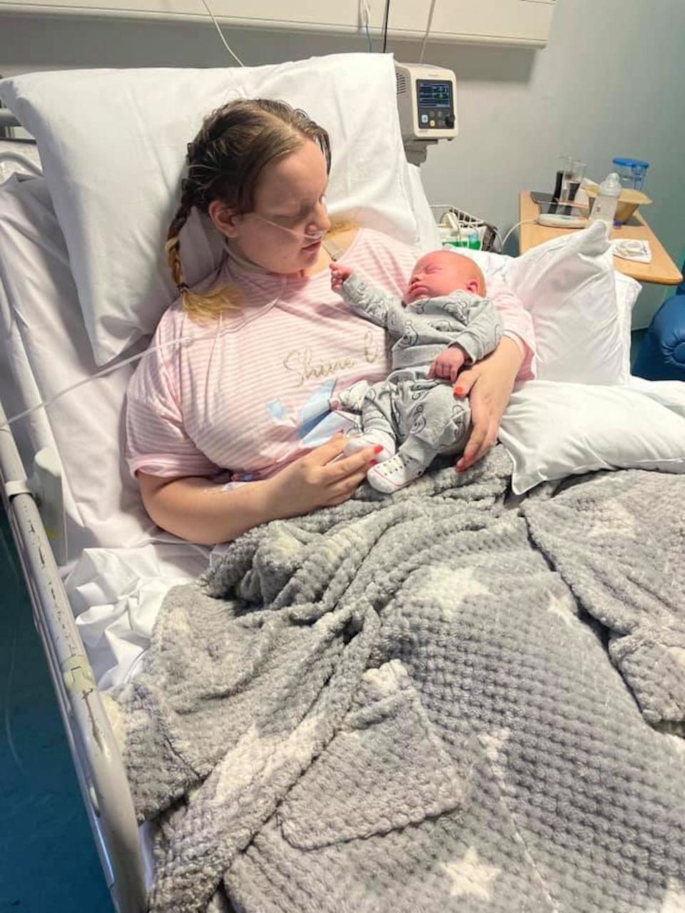 Wright holds her son, Leo, in hospital. (Caters)