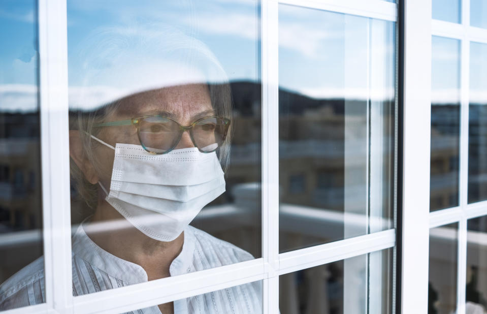 Coronavirus pandemic, senior woman in self quarantine to avoid contagion of infection by virus covid-19. Stays home looking outdoor from the window. Prevention concept