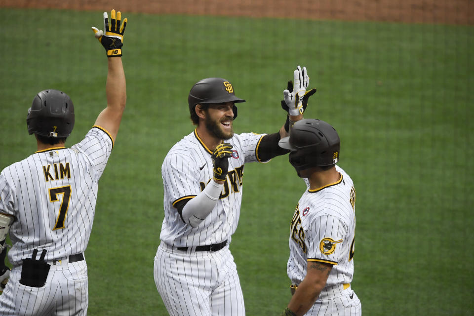 San Diego Padres' Austin Nola (26) is congratulated by Ha-Seong Kim (7) and Tommy Pham (28) after hitting a three-run home run during the third inning of a baseball game against the St. Louis Cardinals, Saturday, May 15, 2021, in San Diego. (AP Photo/Denis Poroy)