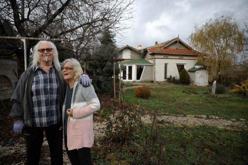 Waldemar Hackstaetter and his wife Hildegard pose for a picture in front of their house in the village of Sirakovo