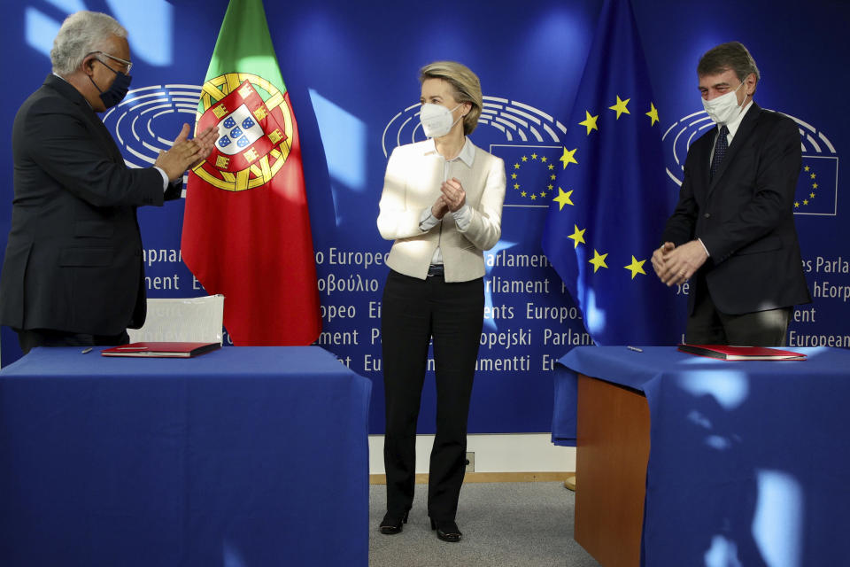 Portugal's Prime Minister Antonio Costa, left, European Commission President Ursula von der Leyen, center, and European Parliament President David Sassoli attend a signing of the EU Recovery and Resilience Facility document, designed to help the bloc with the economic impact of COVID-19, at the European Parliament building in Brussels Friday, Feb. 12, 2021. (AP Photo/Olivier Matthys, Pool)