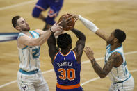 Charlotte Hornets forwards Gordon Hayward, left, and P.J. Washington, right, fight New York Knicks forward Julius Randle (30) for the ball in the first quarter of an NBA basketball game in Charlotte, N.C., Monday, Jan. 11, 2021. (AP Photo/Nell Redmond)