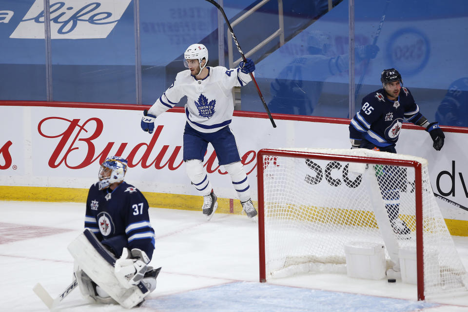 Toronto Maple Leafs' Pierre Engvall (47) celebrates after scoring on Winnipeg Jets goaltender Connor Hellebuyck (37) during the first period of an NHL hockey game Friday, May 14, 2021, in Winnipeg, Manitoba. (John Woods/The Canadian Press via AP)