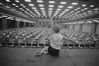 <p>A teacher at the Women's League leads an auditorium full of people in a movement class. </p>