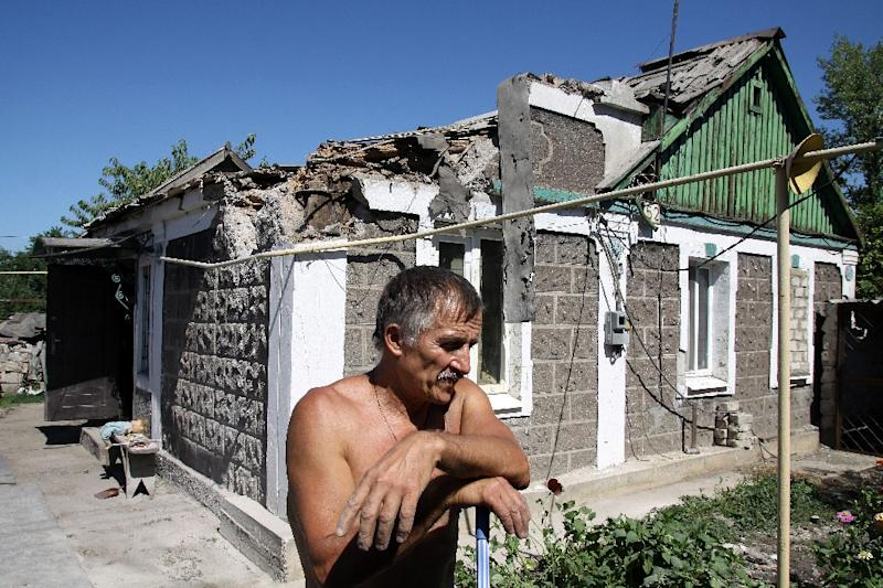 A resident reacts outside his house damaged in shelling between Ukrainian forces and pro-Russian separatists in the village of Oktybrskiyi on August 2, 2015 (AFP Photo/Alexander Gayuk)