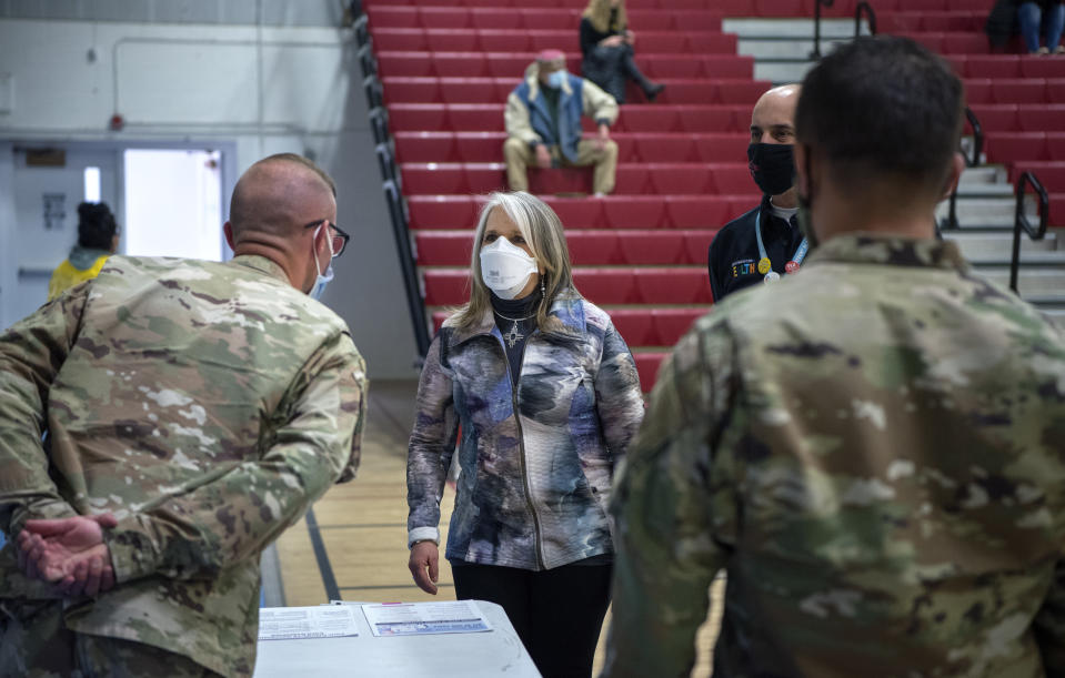 New Mexico Governor Michelle Lujan Grisham talks with National Guardsmen after receiving her Pfizer COVID-19 vaccine during a vaccination event held in the gym at Desert Sage Academy in Santa Fe, N.M. Friday March 26, 2021. (Eddie Moore/The Albuquerque Journal via AP, Pool)