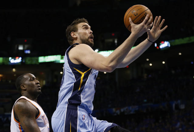 Memphis Grizzlies center Marc Gasol (33) shoots in front of Oklahoma City Thunder center Kendrick Perkins (5) in the first quarter of Game 7 of an opening-round NBA basketball playoff series in Oklahoma City, Saturday, May 3, 2014. (AP Photo/Sue Ogrocki)