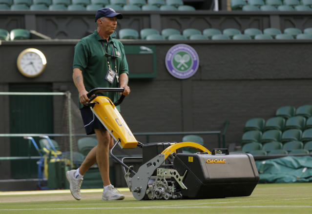 FILE - In this July 13, 2017, file photo, Rick Street mows the grass on Centre Court at the All England Club on day nine at the Wimbledon Tennis Championships in London. At 7:30 a.m. each day of the Wimbledon fortnight, hours before competition begins, the keepers of the grass gather to meticulously prepare the tournament's famous courts for play. (AP Photo/Alastair Grant, File)