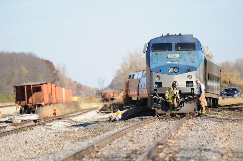 Firefighters inspect the scene of a train derailment just North of Niles, Mich., Sunday, Oct. 21, 2012. About a dozen passengers and crew on an Amtrak train from Chicago to Pontiac, north of Detroit, were injured when two of its locomotives and one or more coaches derailed. (AP Photo/Joseph Weiser) MANDATORY CREDIT