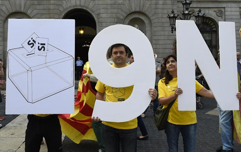 "Pro-independence Catalans hold placards representing a ballot box and the date of the vote ""9N"" on Sant Jaume Square in Barcelona, September 27, 2014 (AFP Photo/Lluis Gene)"
