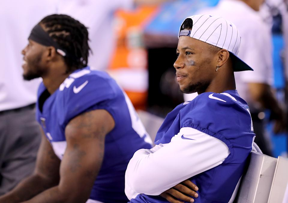 EAST RUTHERFORD, NEW JERSEY - AUGUST 16: Saquon Barkley #26 of the New York Giants looks on from the bench in the second half against the Chicago Bears during a preseason game at MetLife Stadium on August 16, 2019 in East Rutherford, New Jersey. (Photo by Elsa/Getty Images)