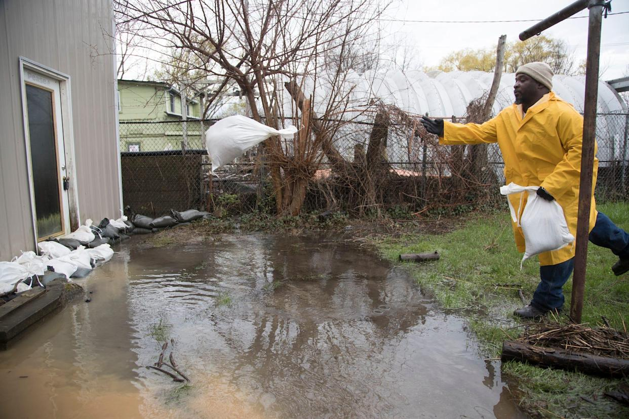 Dwight Miles, an employee from the City of Detroit General Services Department, tosses sandbags in front of a flooded house in the Jefferson Chalmers neighborhood in Detroit, Wednesday, May 1, 2019.