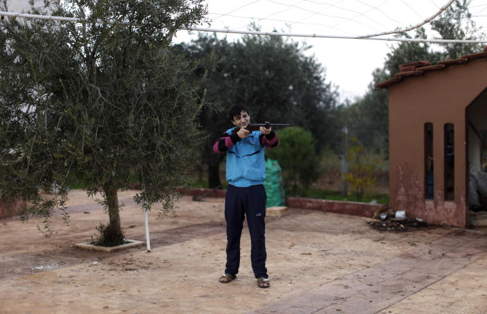 In this Wednesday, Dec. 12, 2012 photo, Alaa, 17, no last name given, a Syrian rebel, practices aiming using an air rifle to save bullets as the price of ammunition is high, in Maaret Ikhwan, near Idlib, Syria. The new Syrian rebel chief, a defected army general who spent months in exile, says he has begun operating inside Syria to unite autonomous anti-regime militias for what he hopes will be the final push against President Bashar Assad. (AP Photo/Muhammed Muheisen)