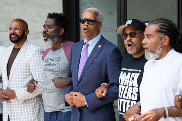 PHOTO: Rep. Hank Johnson and Cliff Albright, second from right, co-founder of Black Voters Matter, sing before being arrested during a protest to support voting rights outside of Hart Building in Washington, July 22, 2021. (Tom Williams/CQ-Roll Call via Getty Images)