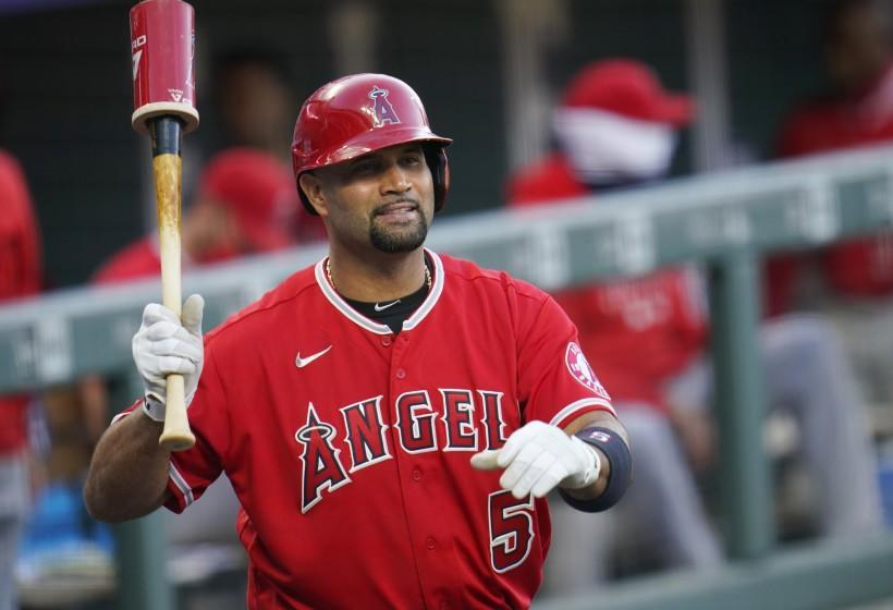 Los Angeles Angels designated hitter Albert Pujols waves to players in the Colorado Rockies.
