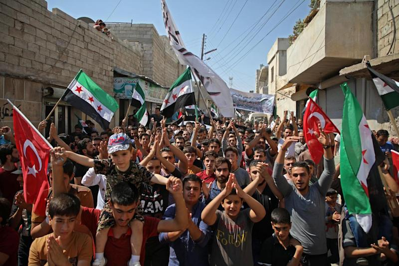 Syrians chant slogans and wave flags of the opposition and of Turkey during demonstration against the Assad regime yesterday, in the rebel-held town of Hazzanu, northwest of Idlib. (AFP/Getty/Aeref Watad)