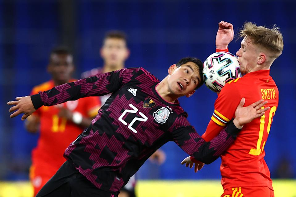 CARDIFF, WALES - MARCH 27: Hirving Lozano of Mexico and Matthew Smith of Wales battle for the ball  during the International Friendly match between Wales and Mexico at Cardiff City Stadium on March 27, 2021 in Cardiff, Wales. Sporting stadiums around Wales remain under strict restrictions due to the Coronavirus Pandemic as Government social distancing laws prohibit fans inside venues resulting in games being played behind closed doors. (Photo by Michael Steele/Getty Images)