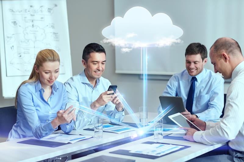 Several people working around a table, their devices connected by cloud-based software
