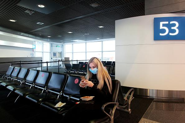A woman waiting to travel to Brisbane is seen wearing a face mask at the Sydney Domestic Airport Terminal.