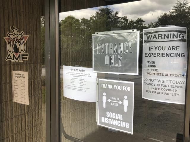 Signs related to COVID-19 are displayed at the AMF bowling alley Friday, April 24, 2020, in Conyers, Ga. Like many industries in America and around the world, bowling has taken a huge financial blow because of lockdown measures meant to contain the highly contagious coronavirus. (AP Photo/Paul Newberry)