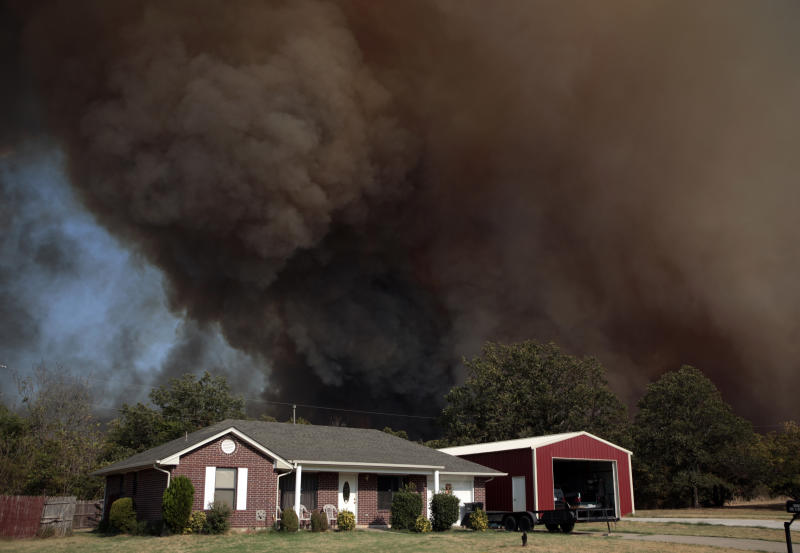 A smoke surrounds home during a large wildfire Friday, Aug. 3, 2012 in Luther, Okla. A wildfire whipped by gusty, southerly winds swept through rural woodlands north and south of Oklahoma City on Friday, burning several homes as firefighters struggled to contain it in 113-degree heat. (AP Photo/The Oklahoman, Sarah Phipps) TABLOIDS OUT