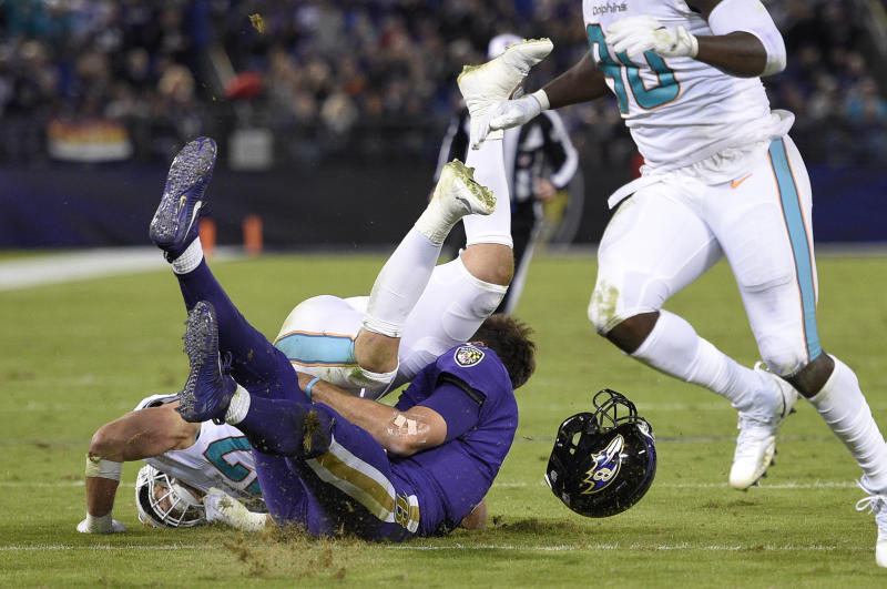 FILE - In this Oct. 26, 2017, file photo, Miami Dolphins middle linebacker Kiko Alonso, top left, collides with Baltimore Ravens quarterback Joe Flacco as Flacco slides on the field after rushing the ball in the first half of an NFL football game in Baltimore. Flacco was the Super Bowl MVP and the NFL's highest-paid quarterback just a few years ago. After injuries shortened his last two seasons, Flacco is now in New York with a new role: as a backup to Sam Darnold. (AP Photo/Nick Wass, File)