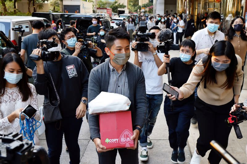 i-Cable TV news journalist leaves with a box after being laid off in Hong Kong