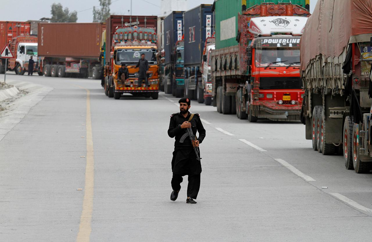 A policeman walks in front of supply trucks carrying containers, after the opening of Pakistan Afghan Torkham border, in Landi Kotal, Pakistan March 21, 2017. REUTERS/Fayaz Aziz