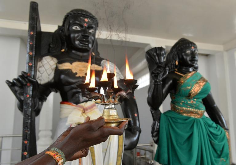 A Hindu priest holds a lit coconut oil lamp in front of statues of Prince Vijaya and demon Princess Kuveni (R) at the Sri Subramaniam temple in Matara on March 7, 2014