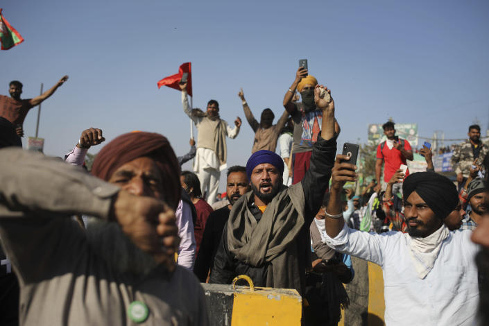 Protesting farmers shout slogans as they attempt to move towards Delhi, at the border between Delhi and Haryana state, Friday, Nov. 27, 2020. Thousands of agitating farmers in India faced tear gas and baton charge from police on Friday after they resumed their march to the capital against new farming laws that they fear will give more power to corporations and reduce their earnings. While trying to march towards New Delhi, the farmers, using their tractors, cleared concrete blockades, walls of shipping containers and horizontally parked trucks after police had set them up as barricades and dug trenches on highways to block roads leading to the capital. (AP Photo/Altaf Qadri)