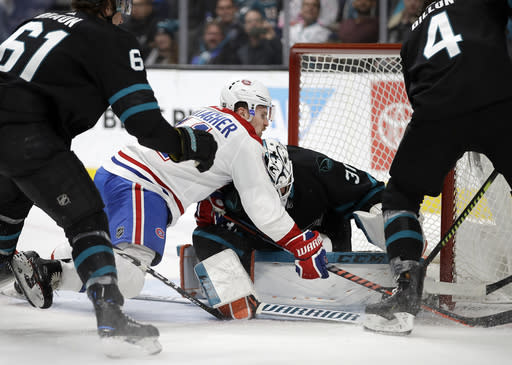 Montreal Canadiens' Brendan Gallagher, center, shoots against San Jose Sharks goalie Martin Jones during the second period of an NHL hockey game Thursday, March 7, 2019, in San Jose, Calif. (AP Photo/Ben Margot)