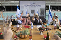 """Israeli activists wear masks depicting Israeli Prime Minister Benjamin Netanyahu and other ministers during a mock cabinet meeting protesting the government's response to the health and economic crisis in Tel Aviv, Israel, Sunday, Sept. 6, 2020. Hebrew reads: """"Detached government meeting"""" . (AP Photo/Sebastian Scheiner)"""