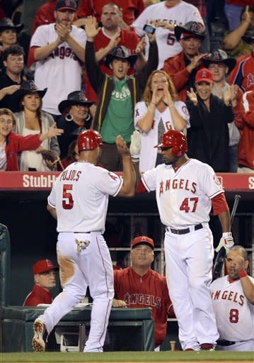 Los Angeles Angels' Albert Pujols, left, is congratulated by Howard Kendrick after scoring on an error by Texas Rangers third baseman Adrian Beltre during the sixth inning of a baseball game, Saturday, June 2, 2012, in Anaheim, Calif. (AP Photo/Mark J. Terrill)