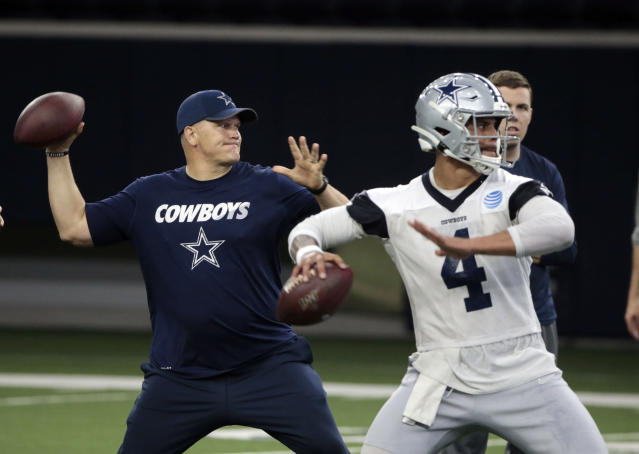 FILE - In this Wednesday, May 22, 2019 file photo, Dallas Cowboys quarterbacks coach Jon Kitna throws the ball alongside Dak Prescott (4) during NFL football practice in Frisco, Texas. Jon Kitna is back in the NFL with one of the quarterbacks former teams in the Dallas Cowboys after coaching high school football for seven years. Kitnas return has plenty to do with his strong relationship with coach Jason Garrett. (AP Photo/Michael Ainsworth, File)