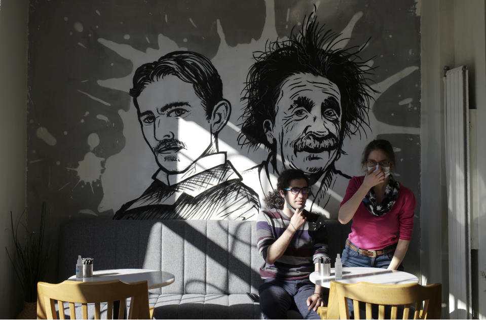 People sit in a coffee shop as cafes, restaurants and other eateries reopened in some provinces across the country, in Ankara, Turkey, Wednesday, March 3, 2021. The businesses are allowed to operate at half-capacity between the hours of 7:00 a.m. and 07:00 p.m. as coronavirus restrictions are eased. (AP Photo/Burhan Ozbilici)